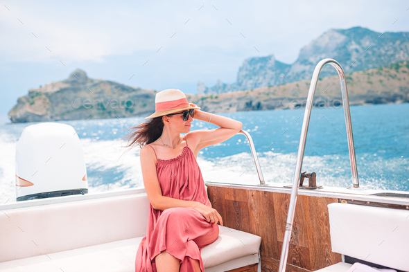 Woman in hat and dress sailing on boat in clear open sea - Stock Photo - Images