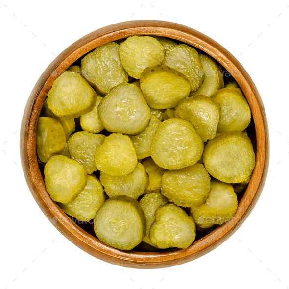 Pickled cucumber discs, known as pickle or gherkin, in wooden bowl - Stock Photo - Images