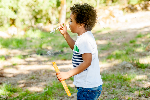 Happy african boy playing with soap bubbles in nature - Stock Photo - Images