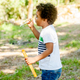 Happy african boy playing with soap bubbles in nature - PhotoDune Item for Sale