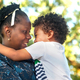 Profile view of an African mom happily hugging her child in nature. - PhotoDune Item for Sale