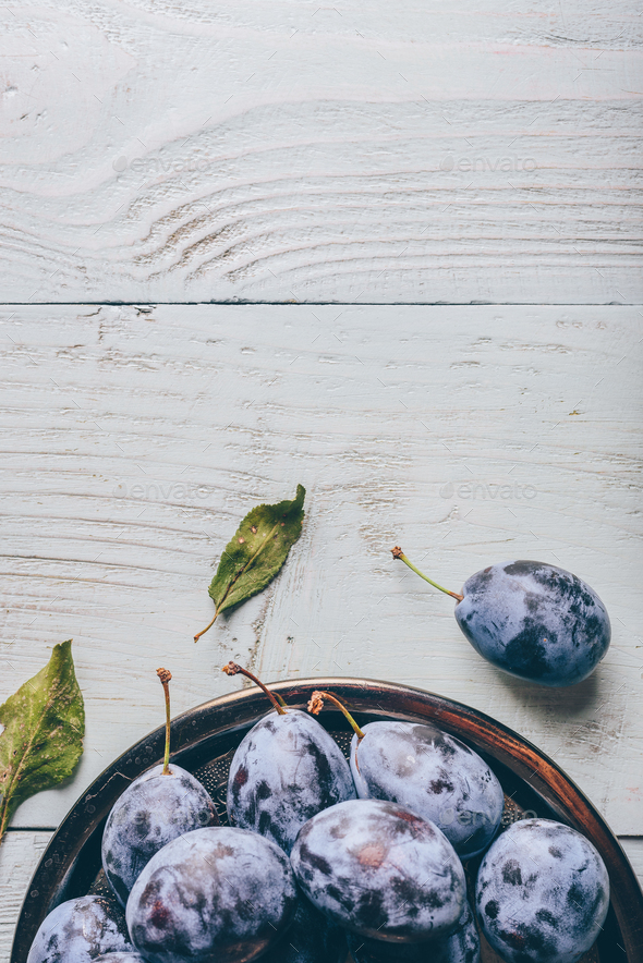 Plums on plate over wooden surface - Stock Photo - Images