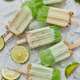 Lime and cream homemade popsicles or ice creams placed with ice cubes on gray stone backdrop - PhotoDune Item for Sale