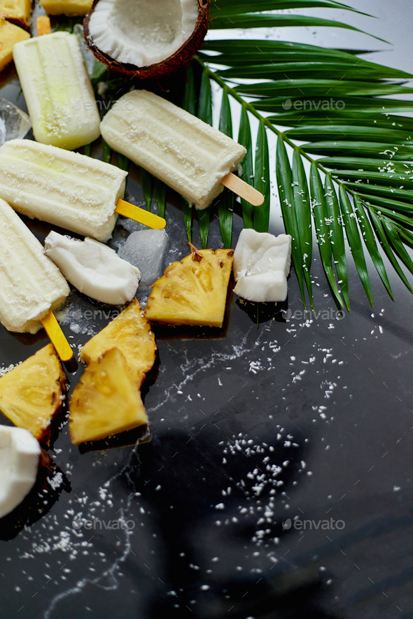 Homemade pineapple coconut popsicles on stone background. Summer food concept with copy space - Stock Photo - Images