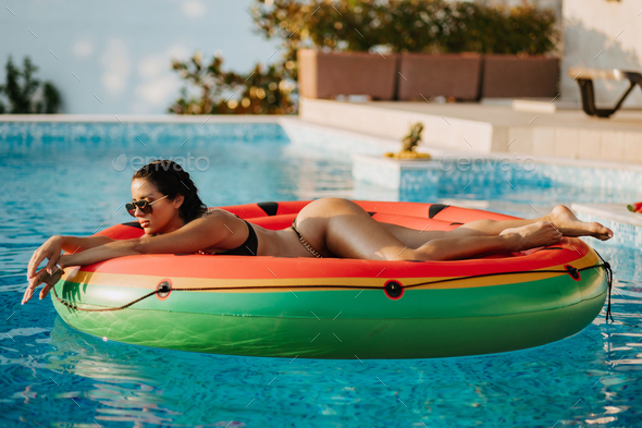 sexy woman relax in swimming pool on inflatable fun beach floaty outdoors - Stock Photo - Images