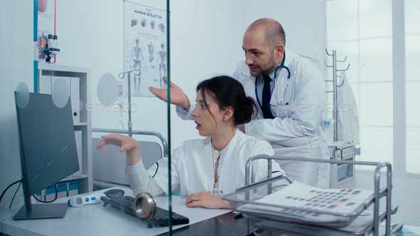 Medical staff examining scan on PC - Stock Photo - Images