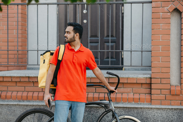 Work in city. Serious deliveryman with beard with backpack and bicycle, holding smartphone and - Stock Photo - Images