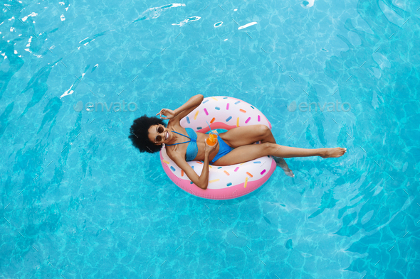 Sexy African American woman with summer drink relaxing on inflatable ring at swimming pool, overhead