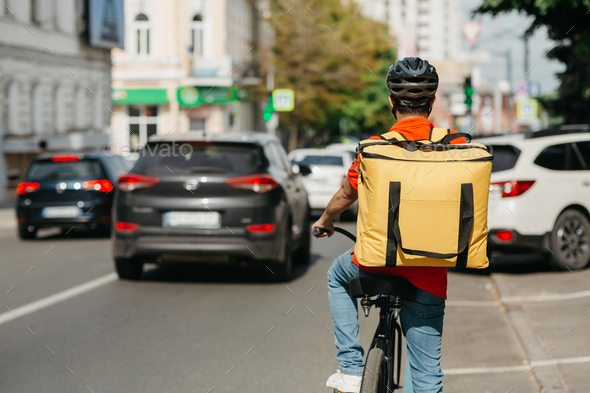 Male courier with helmet and big yellow backpack ride on bicycle along road on street - Stock Photo - Images