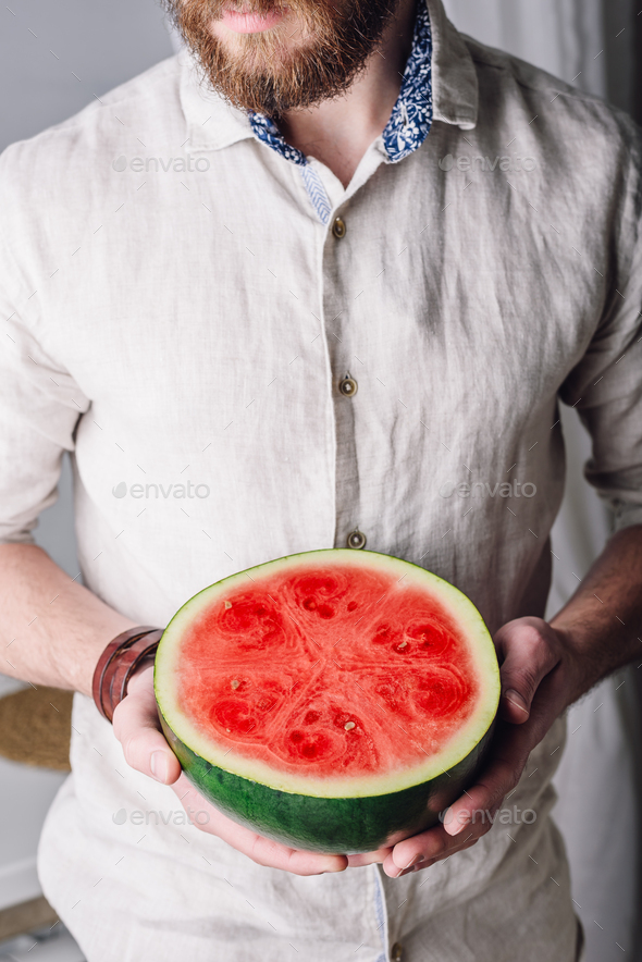 Bearded man with half of watermelon - Stock Photo - Images