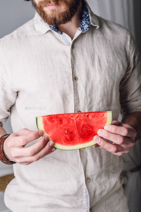 Bearded man in shirt holds in hands slice of watermelon - Stock Photo - Images