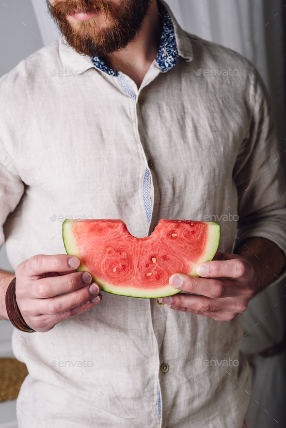 Bearded man in shirt with bitten off piece of watermelon - Stock Photo - Images