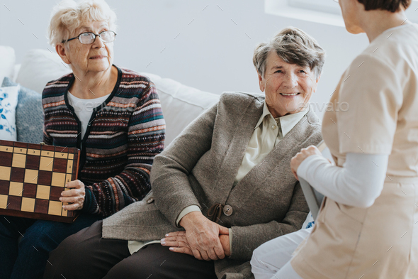 Older ladies sit on a couch and talk to a nurse at a local nursing home - Stock Photo - Images