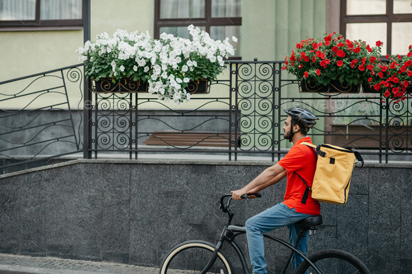 Courier carry out orders for delivery of goods. Man in helmet and big yellow backpack rides bicycle - Stock Photo - Images