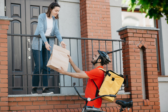 Customer, delivery and courier. Girl takes bag from man with backpack and bicycle, near front door - Stock Photo - Images