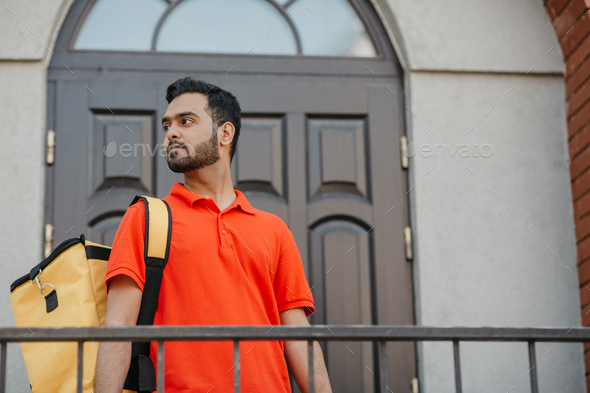City delivery service and search customer address. Attractive man with yellow backpack, near front - Stock Photo - Images