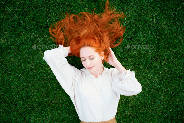 Beautiful girl with red hair lying on green grass with closed eyes - Stock Photo - Images