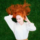 Beautiful girl with red hair lying on green grass with closed eyes - PhotoDune Item for Sale