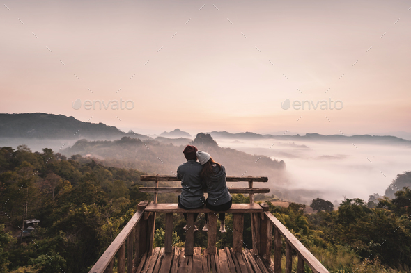 Young couple traveler looking at sea of mist and sunset over the mountain at Mae Hong Son, Thailand - Stock Photo - Images