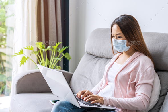 Young woman wearing medical mask sitting at living room and working on laptop at home - Stock Photo - Images