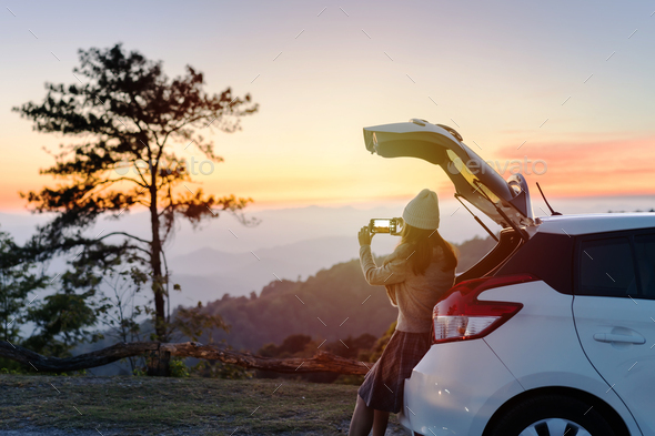 Young woman traveler looking beautiful landscape with car on road trip - Stock Photo - Images