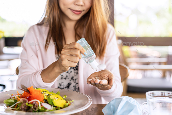 Young woman using alcohol gel sanitizer to avoid infections corona virus and bacteria before meals - Stock Photo - Images