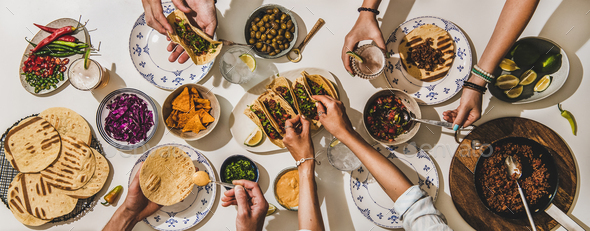 Family or friends having Mexican style Taco dinner with beer - Stock Photo - Images