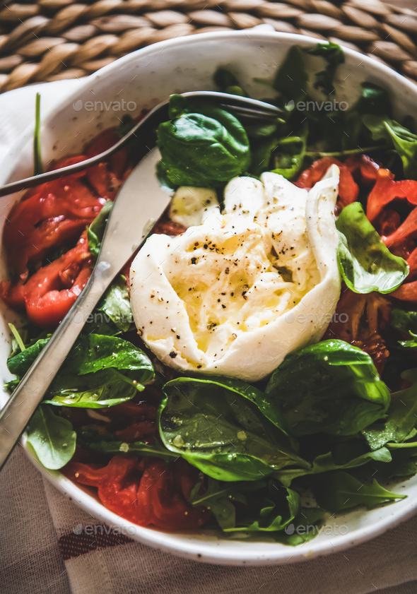 Italian salad with Buratta cheese in white bowl, close-up - Stock Photo - Images