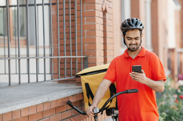 Delivery address. Smiling courier in uniform and helmet with backpack and bike watching at - Stock Photo - Images