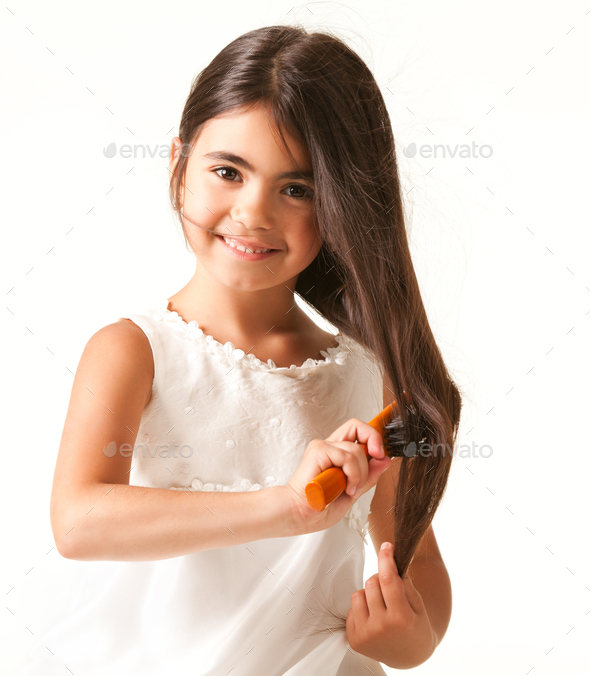 Cute girl in white dress combing brown hair - Stock Photo - Images