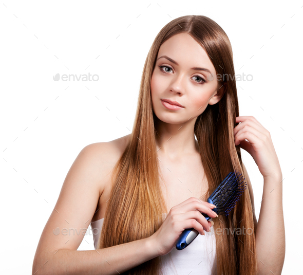 Woman combing long shiny brown hair - Stock Photo - Images