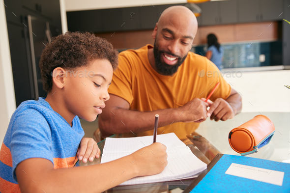 African American Father Helping Son Studying Homework In Kitchen - Stock Photo - Images