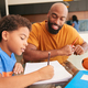 African American Father Helping Son Studying Homework In Kitchen - PhotoDune Item for Sale