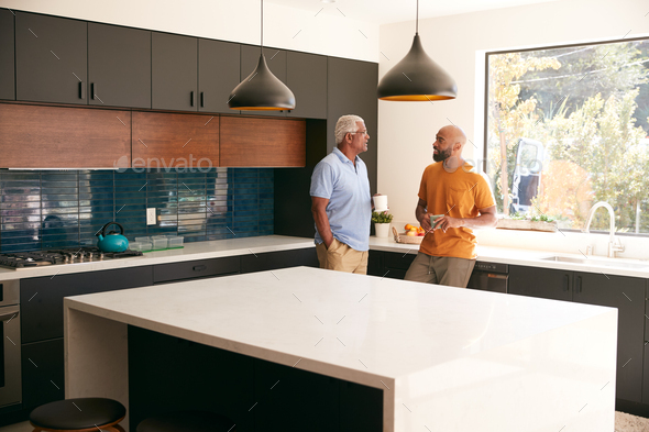 Senior Father Talking And Drinking Coffee With Adult Son In Kitchen At Home - Stock Photo - Images