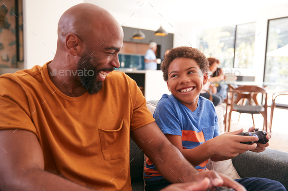 African American Father And Son Sitting On Sofa At Home Playing Video Game Together - Stock Photo - Images