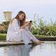 Attractive stylish girl sitting near pool dreamily using smartphone on beautiful modern villa - PhotoDune Item for Sale