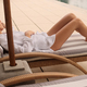 Attractive stylish girl in white shirt resting lying on deck chair on villa - PhotoDune Item for Sale