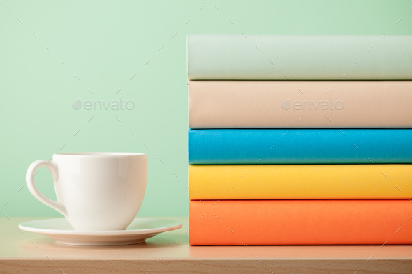 Stack of books and cup on wooden table - Stock Photo - Images