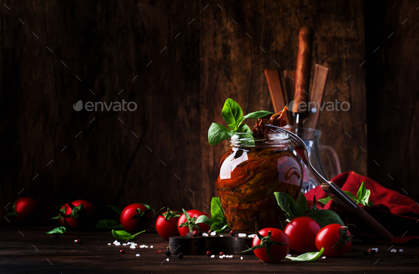 Dried tomatoes in olive oil with green basil and spices in glass jar - Stock Photo - Images
