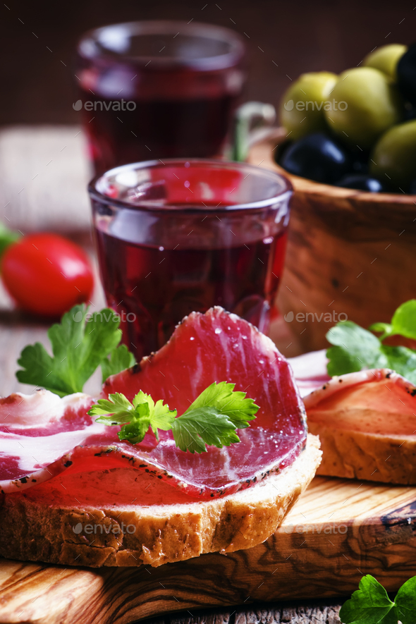 Small sandwiches with jerked ham, olives, tomatoes and red wine - Stock Photo - Images