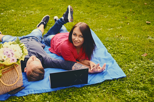 Attractive couple lying using a laptop on a picnic. - Stock Photo - Images