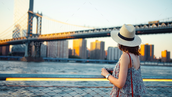 Young woman with a retro camera at the Manhattan Bridge - Stock Photo - Images