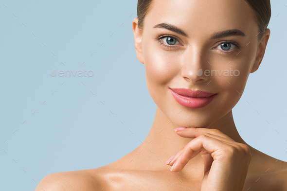 Beauty woman skin care beautiful female hand touching face cosmetic girl model over blue background - Stock Photo - Images