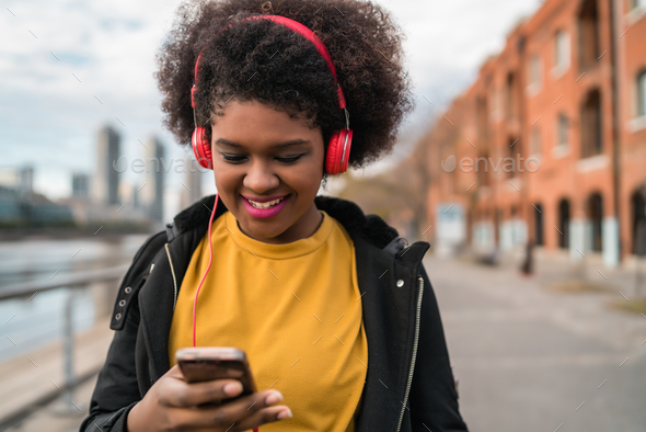 Woman with mobile phone and headphones - Stock Photo - Images