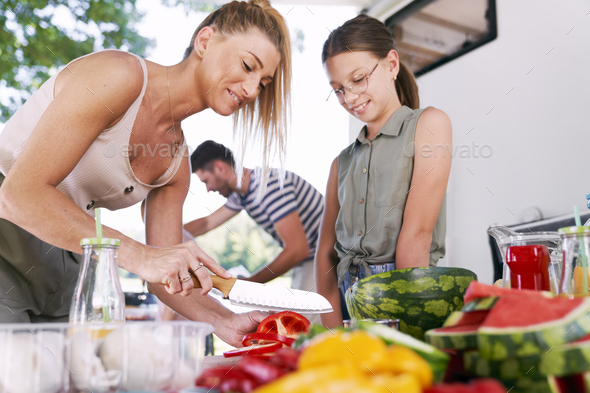 Mother and daughter preparing food for picnic - Stock Photo - Images