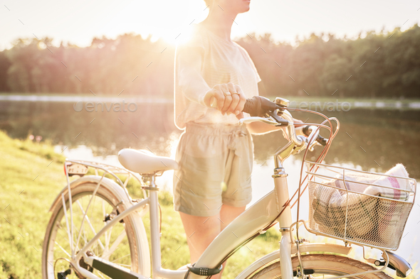 Close up of woman with bike by the lake - Stock Photo - Images