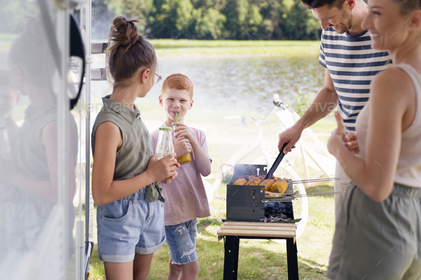 Family having barbecue during camper trip - Stock Photo - Images