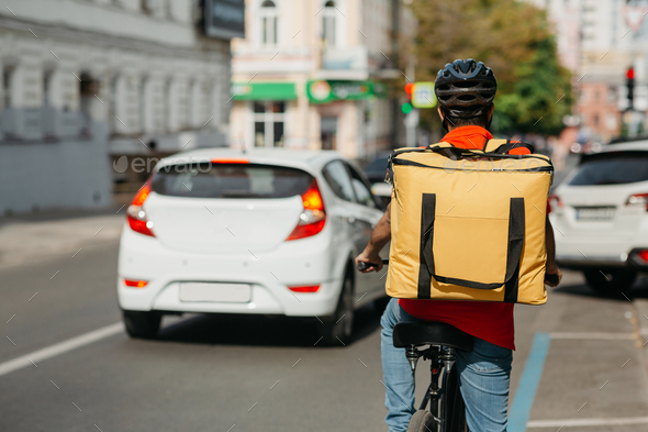 Fast bicycle courier. Delivery man in safety helmet, with bag rides a bicycle - Stock Photo - Images