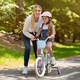 Mom Teaching Daughter To Ride Bicycle Spending Day In Park - PhotoDune Item for Sale