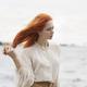 Focused redhead female looking away on riverside - PhotoDune Item for Sale